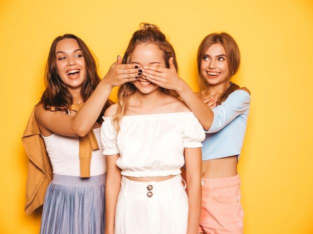Drei junge schöne lächelnde hippie-mädchen in der modischen sommerkleidung sexy sorglose frauen, die nahe gelber wand aufwerfen modelle, die ihren freund überraschen sie bedecken ihre augen und von hinten umarmen