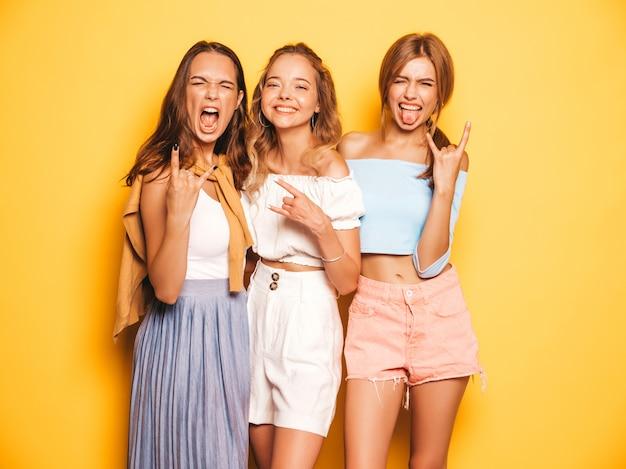 Drei junge schöne lächelnde hippie-mädchen in der modischen sommerkleidung. sexy sorglose frauen, die nahe gelber wand aufwerfen. positive modelle, die verrückt gehen und spaß haben. sie zeigen rock-and-rollzeichen