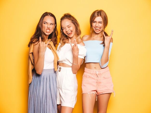Drei junge schöne lächelnde hippie-mädchen in der modischen sommerkleidung. sexy sorglose frauen, die nahe gelber wand aufwerfen. positive modelle, die verrückt gehen und spaß haben. zeigen des rock-and-rollzeichens