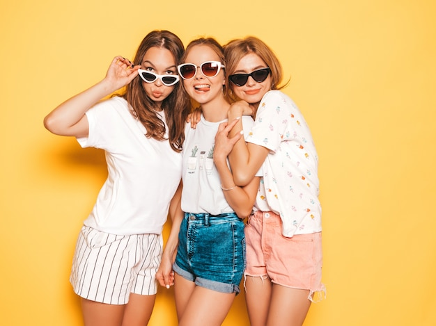 Drei junge schöne lächelnde hippie-mädchen in der modischen sommerkleidung. sexy sorglose frauen, die nahe gelber wand aufwerfen. positive modelle, die verrückt werden und spaß haben. umarmen in der sonnenbrille