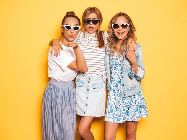 Drei junge schöne lächelnde hippie-mädchen in der modischen sommerkleidung. sexy sorglose frauen, die nahe gelber wand aufwerfen. positive models, die spaß an sonnenbrillen haben