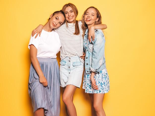 Drei junge schöne lächelnde hippie-mädchen in der modischen sommerkleidung. sexy sorglose frauen, die nahe gelber wand aufwerfen. positive models, die spaß haben
