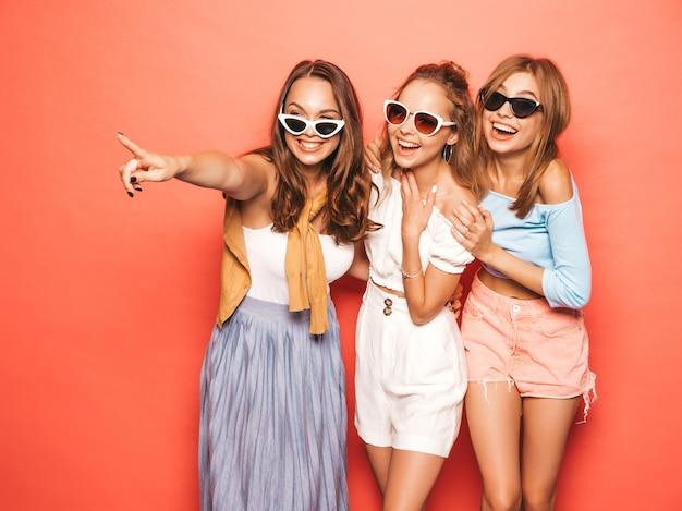 Drei junge schöne lächelnde hippie-mädchen in der modischen sommerkleidung. sexy sorglose frauen, die nahe rosa wand aufwerfen. positive modelle, die spaß haben. zeigen auf shopverkäufe