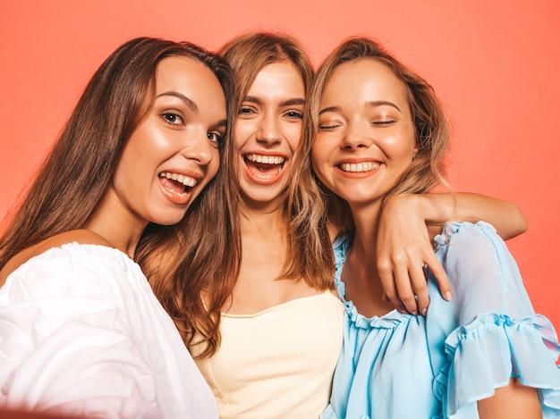 Drei junge schöne lächelnde hippie-mädchen in der modischen sommerkleidung. sexy sorglose frauen, die nahe rosa wand aufwerfen. positive modelle, die verrückt werden. selfie-selbstporträtfotos auf smartphone machen
