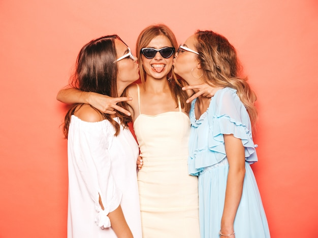 Drei junge schöne lächelnde hippie-mädchen in der modischen sommerkleidung. sexy sorglose frauen, die nahe rosa wand aufwerfen. positive modelle, die verrückt werden und spaß haben. ihren freund in der backe küssen