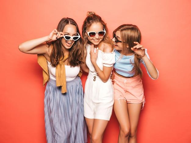 Drei junge schöne lächelnde hippie-mädchen in der modischen sommerkleidung. sexy sorglose frauen, die nahe rosa wand aufwerfen. positive models, die spaß an sonnenbrillen haben