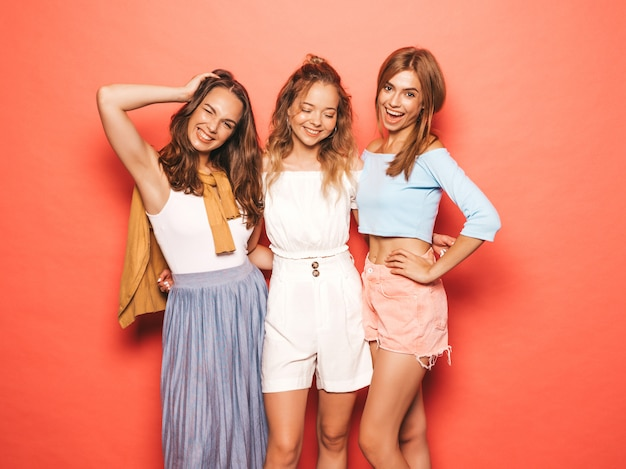 Drei junge schöne lächelnde hippie-mädchen in der modischen sommerkleidung. sexy sorglose frauen, die nahe rosa wand aufwerfen. positive models, die spaß haben