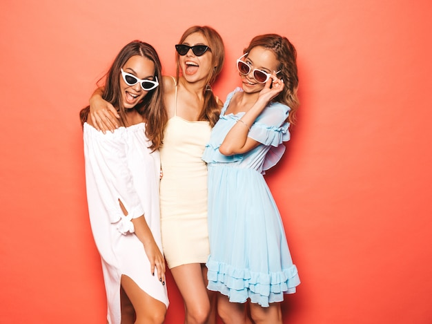 Drei junge schöne lächelnde hippie-mädchen in der modischen sommerkleidung. sexy sorglose frauen, die nahe rosa wand aufwerfen. positive models werden verrückt und haben spaß mit sonnenbrillen