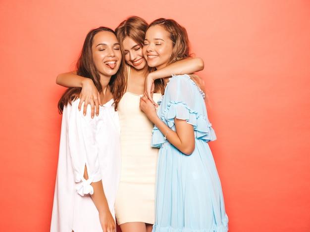 Drei junge schöne lächelnde hippie-mädchen in der modischen sommerkleidung. sexy sorglose frauen, die nahe rosa wand aufwerfen. positive models werden verrückt und haben spaß