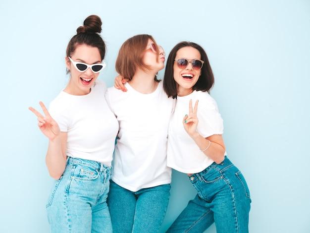 Drei junge schöne lächelnde hipster-frau in trendigen weißen t-shirts und jeans im gleichen sommer