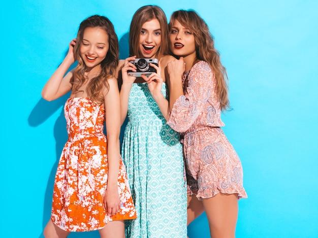 Drei junge schöne lächelnde mädchen in den beiläufigen kleidern des modischen sommers. sexy sorglose frauenaufstellung. fotografieren mit der retro-kamera