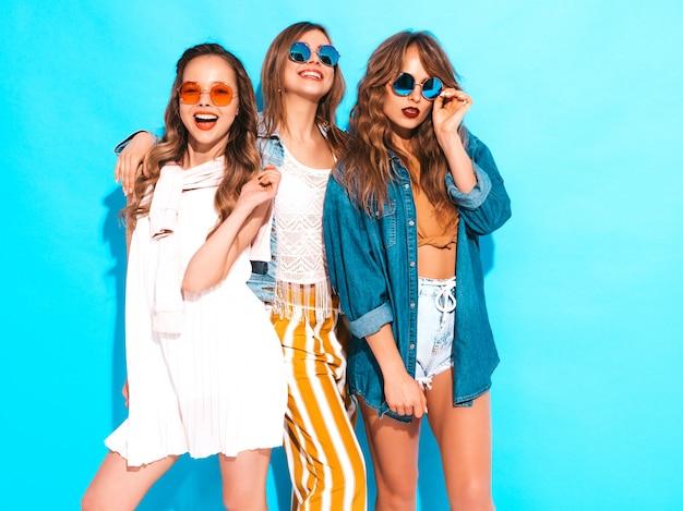Drei junge schöne lächelnde mädchen in den beiläufigen kleidern des modischen sommers. sexy sorglose frauenaufstellung. positive vorbilder