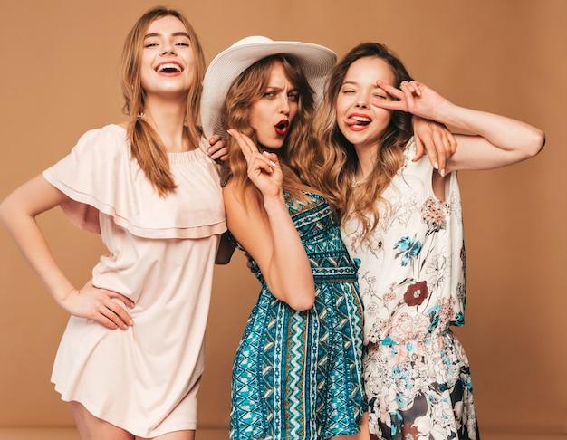 Drei junge schöne lächelnde mädchen in den beiläufigen kleidern des modischen sommers. sexy sorglose frauenaufstellung.