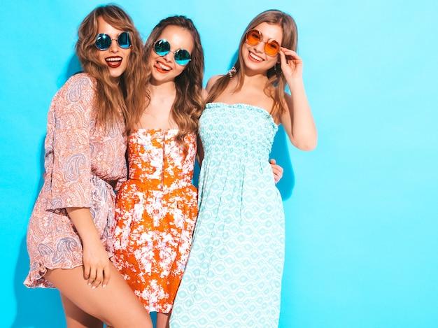 Drei junge schöne lächelnde mädchen in den bunten kleidern des modischen sommers. sexy sorglose frauen mit sonnenbrille.