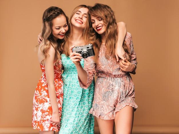 Drei junge schöne lächelnde mädchen in den bunten kleidern des modischen sommers. sexy sorglose frauenaufstellung. fotografieren mit der retro-kamera