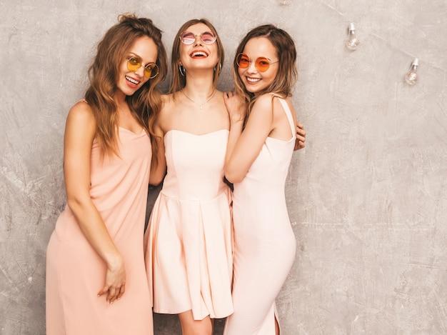 Drei junge schöne lächelnde mädchen in den hellrosa kleidern des modischen sommers. sexy sorglose frauenaufstellung. positive models in runder sonnenbrille haben spaß