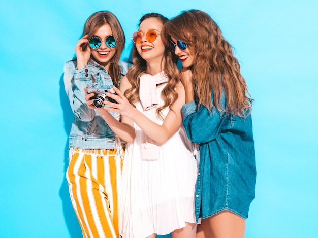 Drei junge schöne lächelnde mädchen in den zufälligen kleidern des modischen sommers und in der sonnenbrille. sexy sorglose frauenaufstellung. fotografieren mit der retro-kamera