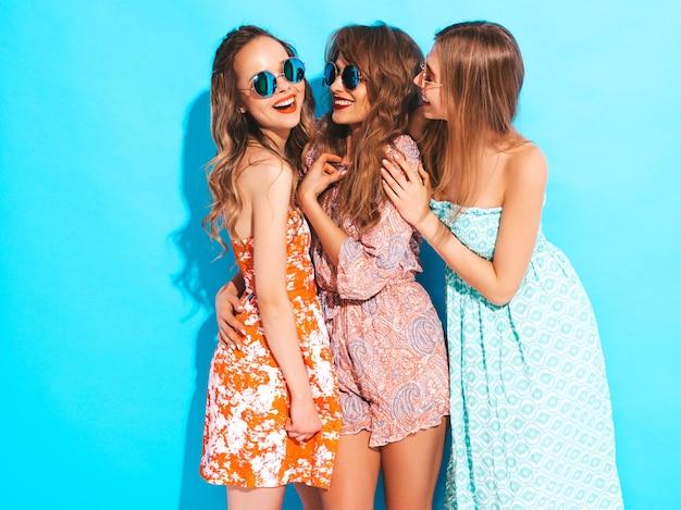Drei junge schöne lächelnde mädchen in den zufälligen kleidern des modischen sommers und in der sonnenbrille. sexy sorglose frauenaufstellung.