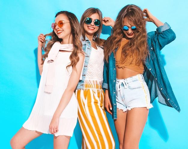 Drei junge schöne lächelnde mädchen in der beiläufigen kleidung des modischen sommers. sexy sorglose frauenaufstellung. positive models in sonnenbrillen