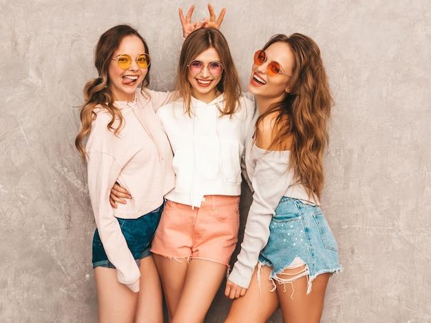 Drei junge schöne lächelnde mädchen in der modischen sommersportkleidung. sexy sorglose frauenaufstellung. models in runden sonnenbrillen, die spaß haben. macht sich mit den fingern hörner auf den kopf