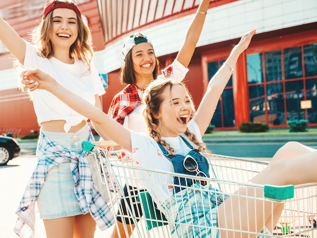 Drei junge schöne mädchen, die spaß im einkaufswagen haben