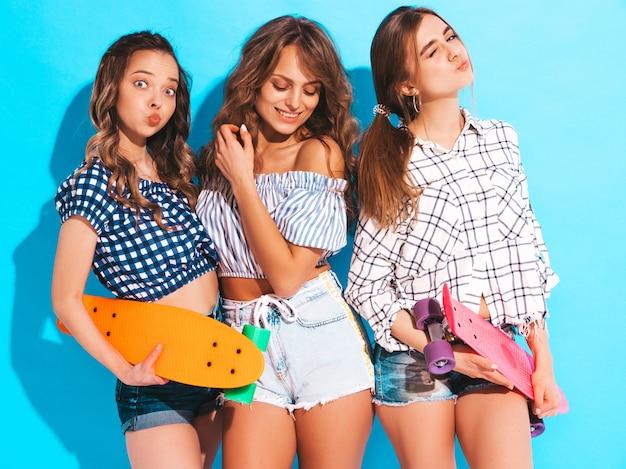 Drei junge stilvolle lächelnde schöne mädchen mit bunten pennyskateboards. frauen in der karierten hemdkleidungsaufstellung des sommers. positive models, die spaß haben