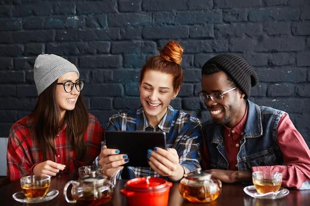 Drei junge stilvolle leute verschiedener rassen, die videos online auf einem generischen digitalen tablet ansehen, während sie zusammen im restaurant speisen
