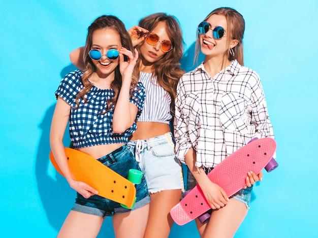 Drei junge stilvolle sexy lächelnde schöne mädchen mit bunten pennyskateboards. frauen in der karierten hemdkleidung des sommers, die in der sonnenbrille aufwirft. positive models, die spaß haben