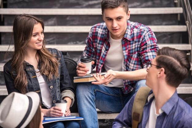 Drei junge studenten, die auf treppen im college lernen.