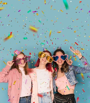 Drei junge teenager-mädchen feiern mit konfetti