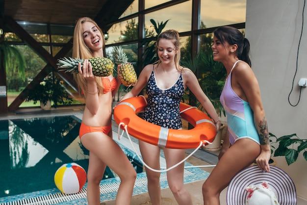 Drei junge weibliche modelle, die in badeanzügen posieren, die ananas, hut und saft am schwimmbad am kurzentrum halten