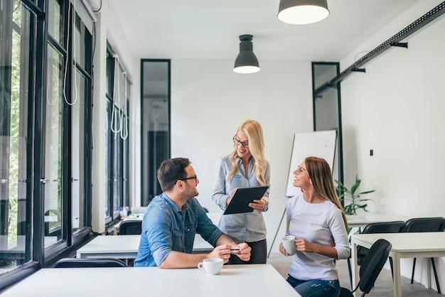 Drei junge zufällige geschäftsleute, die in einem klassenzimmer oder in einem coworkingbüro sprechen.