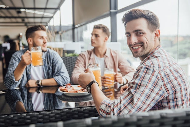 Drei jungen sitzen im café und unterhalten sich mit biergläsern über ihre zukunft