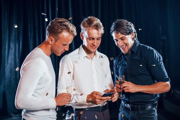 Drei jungs in festlicher kleidung unterhalten sich und schauen auf das telefon.