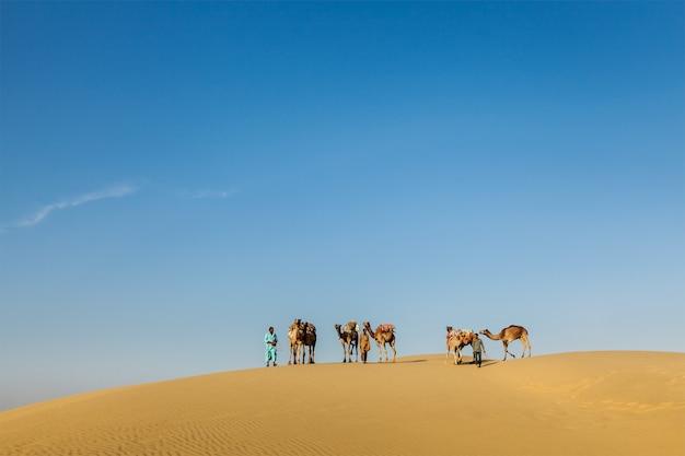 Drei kameltreiber (kameltreiber) mit kamelen in den dünen von thar des