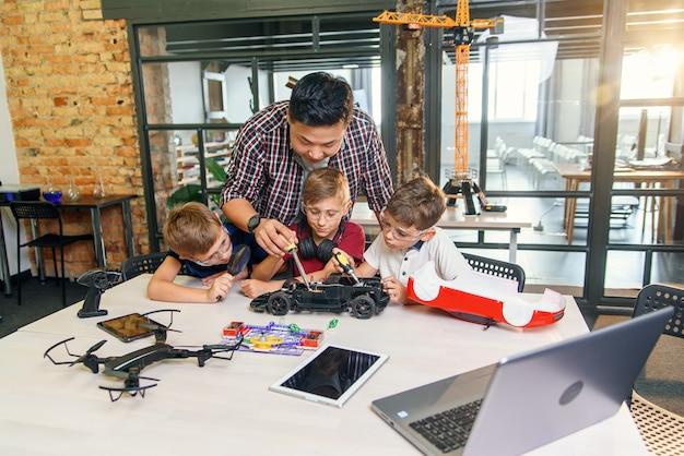 Drei kaukasische schüler mit einem physiklehrer reparieren ein funkgesteuertes spielzeugautomodell.
