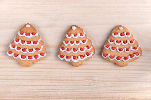 Drei kekse geformten weihnachtsbaum auf einem hölzernen hintergrund