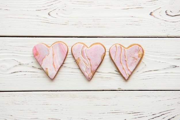 Drei kekse in form von weißen marmorherzen auf hölzernem hintergrund