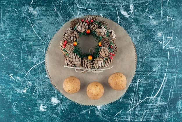 Drei kekse und ein tannenzapfenkranz auf einem brett auf blau.