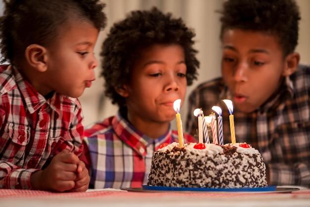 Drei kinder blasen kerzen aus jungen blasen kuchen kerzen aus moment, sie haben auf wichtige gewartet ...