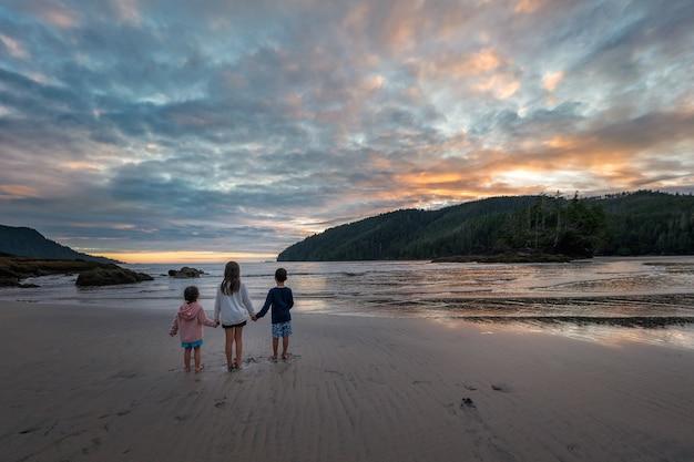 Drei kinder, die hände halten wegschauen auf schönen sonnenuntergang an einem strandanruf san joseph bay beach auf vancouver island in britisch-kolumbien, kanada