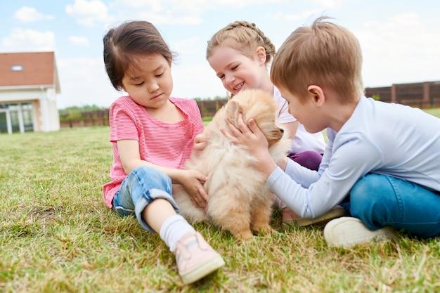 Drei kinder, die mit welpen spielen