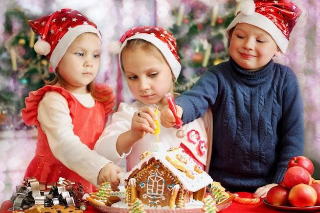 Drei kinder in kappen verziert lebkuchenhaus