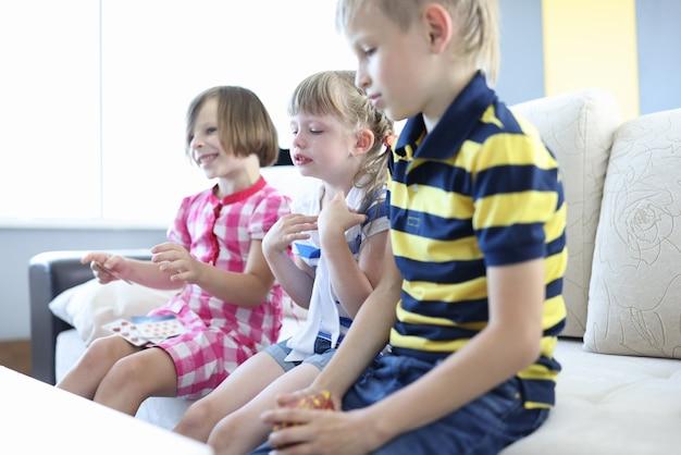 Drei kinder sitzen auf dem sofa im zimmer. junge hält kartenspiel in seinen händen