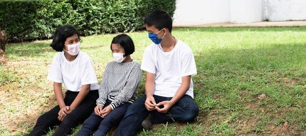 Drei kinder sitzen auf grünem gras im erdgeschoss. sie tragen eine maske, um sich vor krankheiten und neuem normalem leben zu schützen