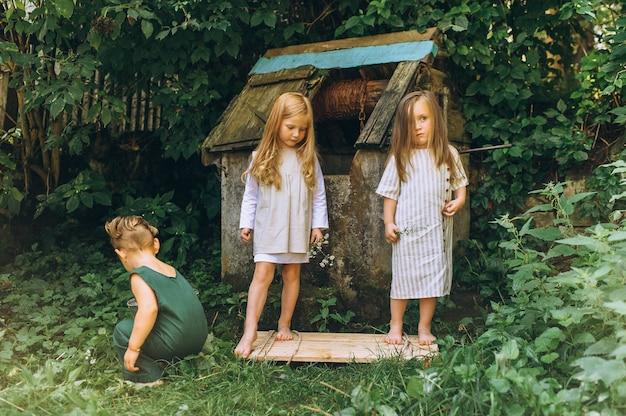 Drei kinder spielen in der nähe des brunnens auf einem hintergrund von gras und bäumen