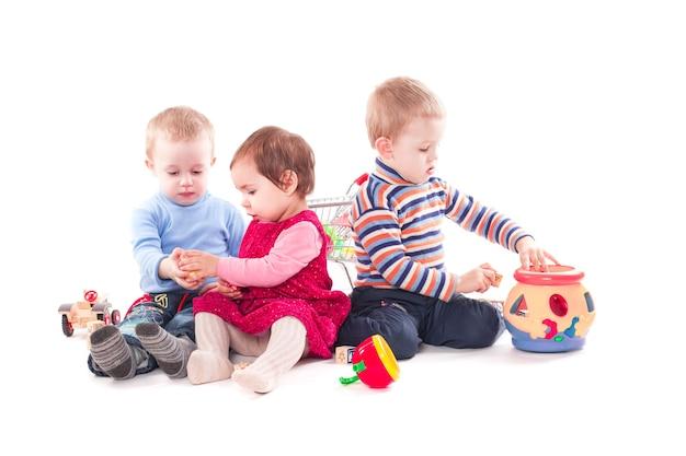 Drei kinder spielen mit spielzeug isoliert auf weiß
