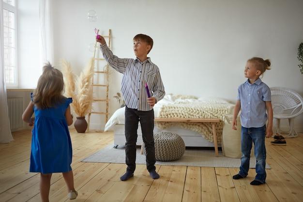 Drei kinder spielen zu hause zusammen. schuljunge in hemd und jeans bläst seifenblasen im geräumigen schlafzimmer, sein kleiner bruder und seine kleine schwester warten darauf, dass sie an die reihe kommen, und stehen um ihn herum auf dem boden