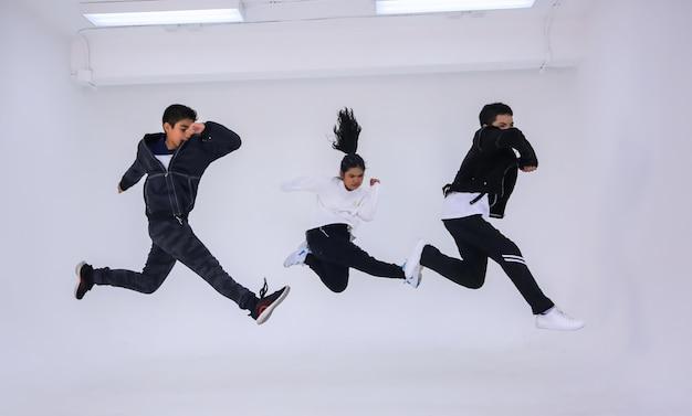 Drei kinder springen und trainer tanzen isoliert auf weißem hintergrund. porträt des kindertänzers, der im studio springt.