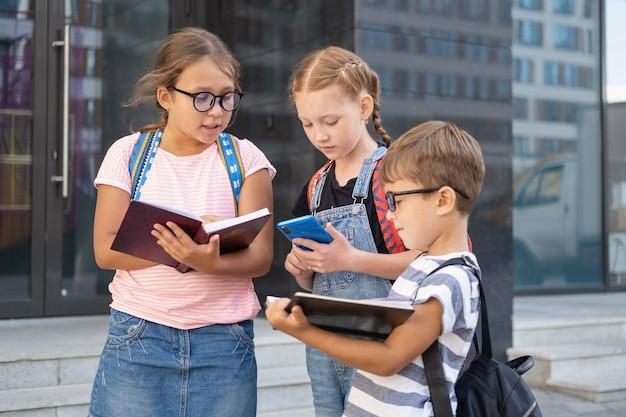 Drei kinder und rucksack stehen und lesen buch, mit telefon im schulhof. zurück zur schule
